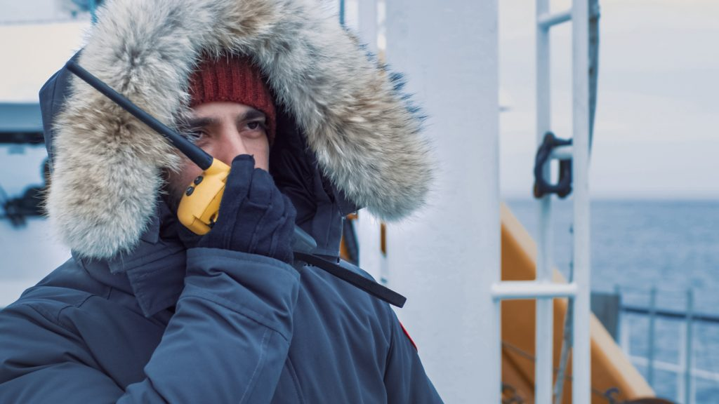 Polar Scientist in Warm Jacket Standing on Ship and Using Radio for Communication. Polar Research Exploration.