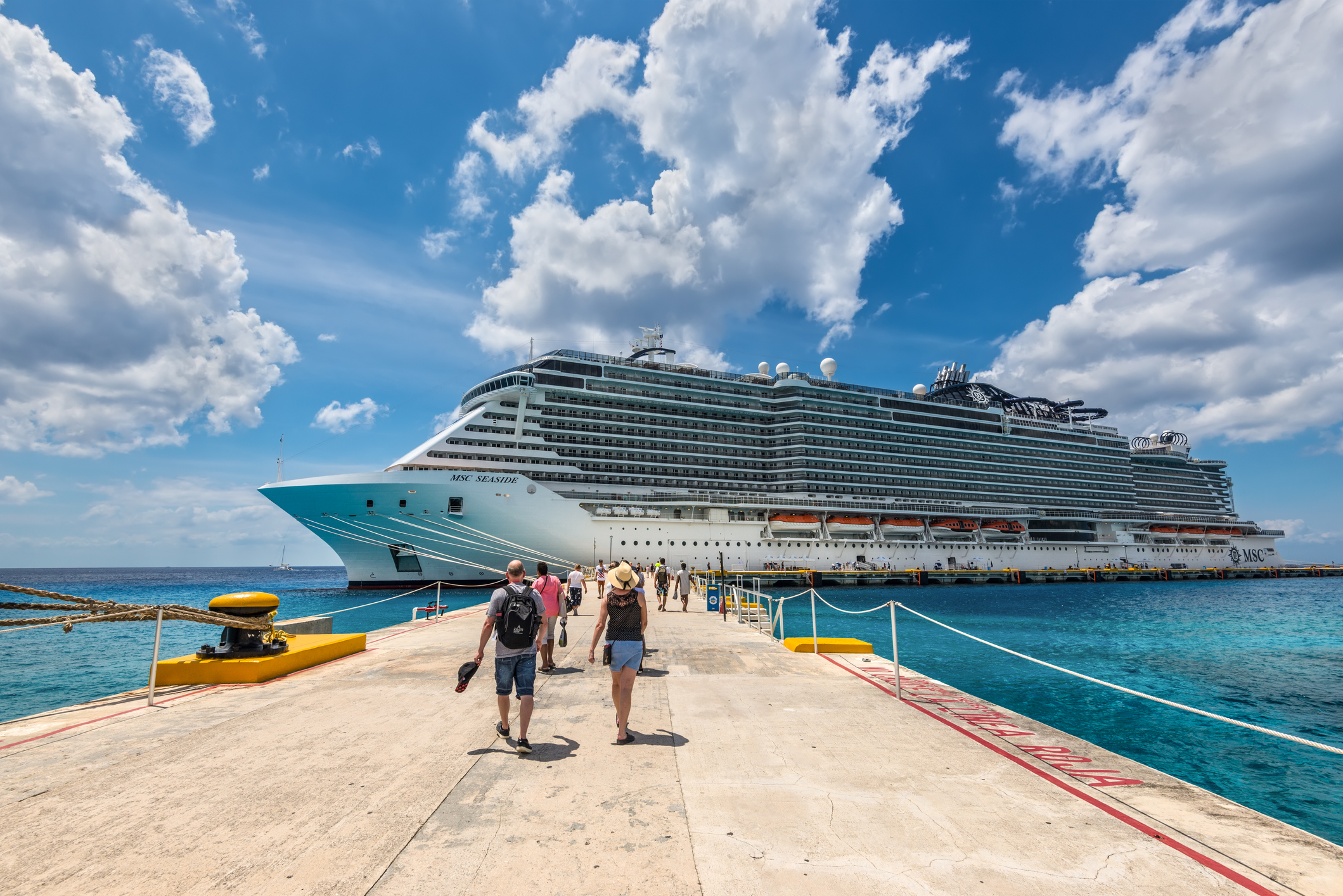 Cruise passengers arrive to the cruise ship to check in and board the MSC Seaside Cruise Ship which sails from Cozumel to Miami.